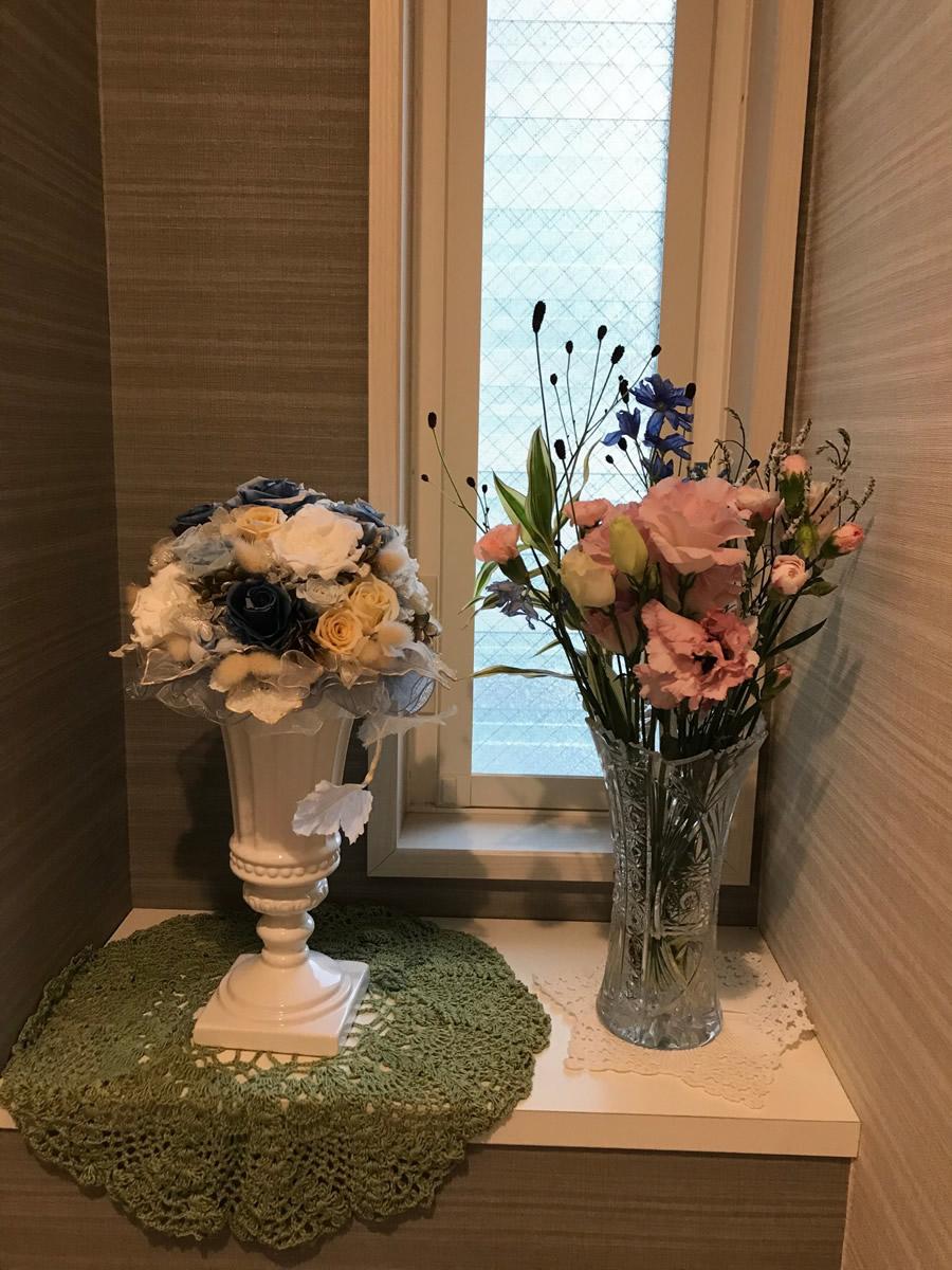 1階トイレ - 薄いピンクとブルーの花に、ねじ花の白とがまの赤茶の差し色を