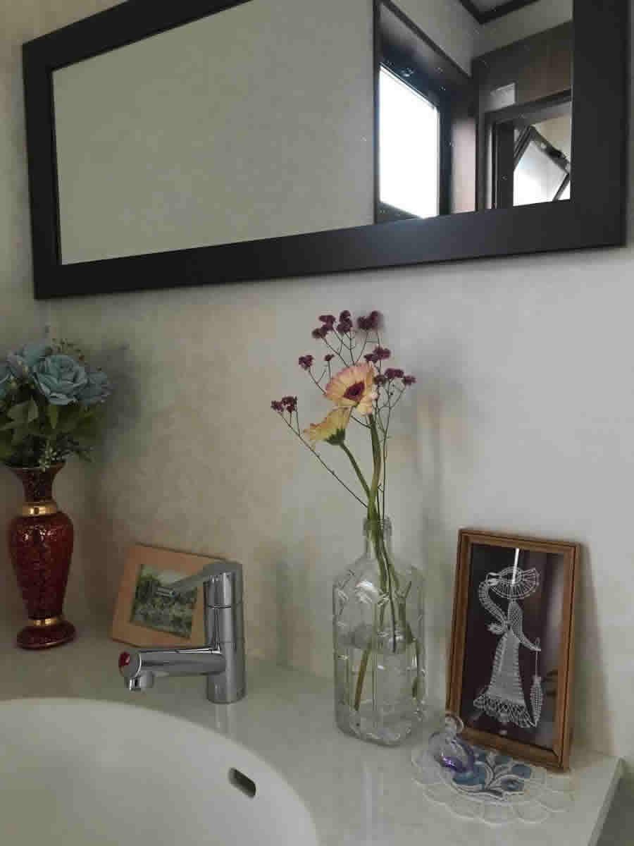 2階トイレ - 薄黄色に花芯と縁の濃ピンクのガーベラに 花芯と同色の小花を ウヰスキーの空き瓶に