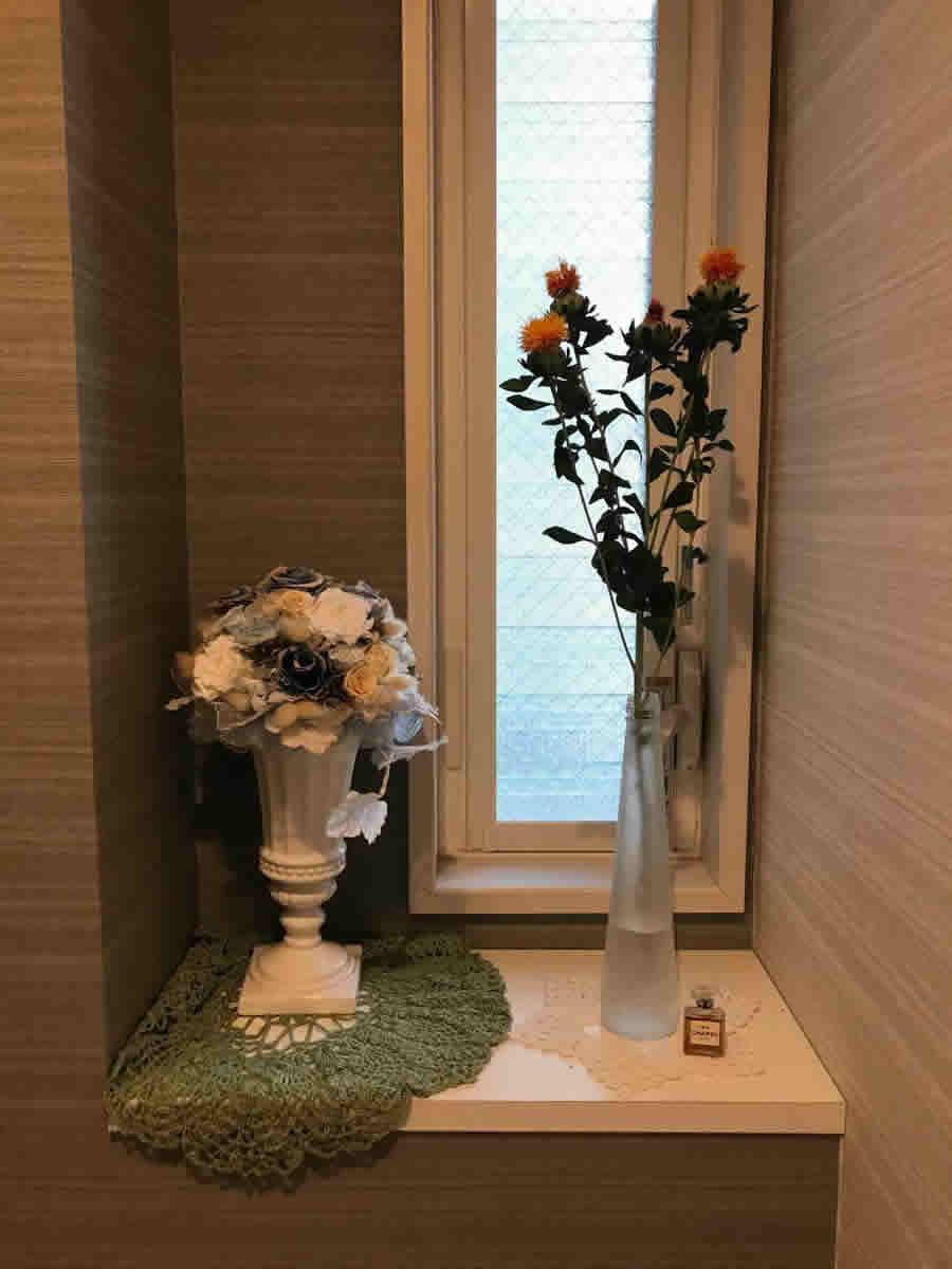 1階トイレ- オレンジ色のアザミのひと枝を