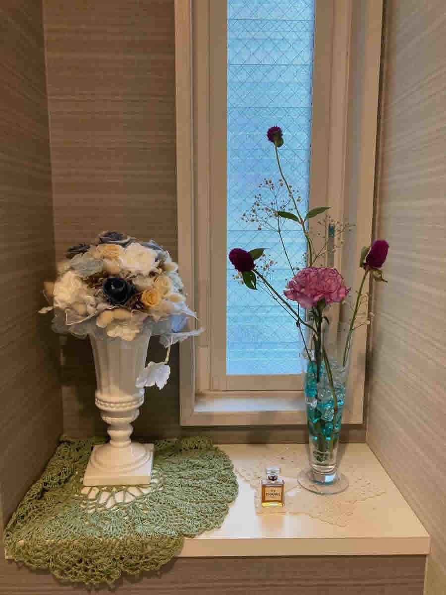 1階トイレ - 濃い縁取りのピンクのカーネーション、紫がかったピンクの千日紅、霞草をビールグラスに