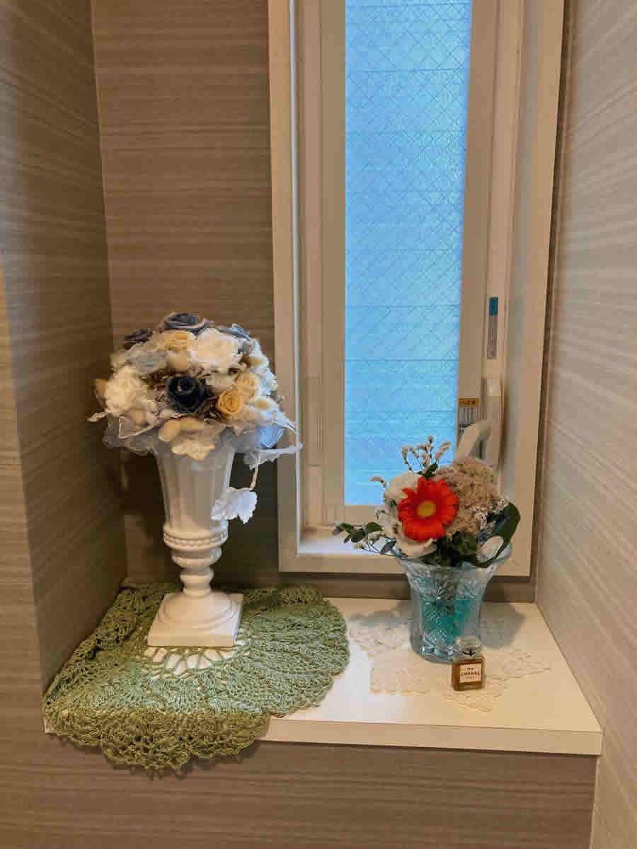 1階トイレ - オレンジのガーベラ、白いトルコ桔梗、細かな花の集まった桜花月に、葉蘭とユーカリと宿根霞草のブーケ